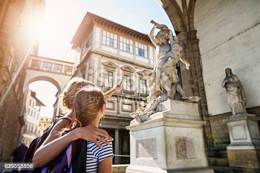 Mother and daughter tourists sightseeing beautiful Italian city of Florence capital of Italian region of Tuscany. The family is standing in Loggia dei Lanzi, an open-air sculpture gallery in the central Piazza della Signoria.