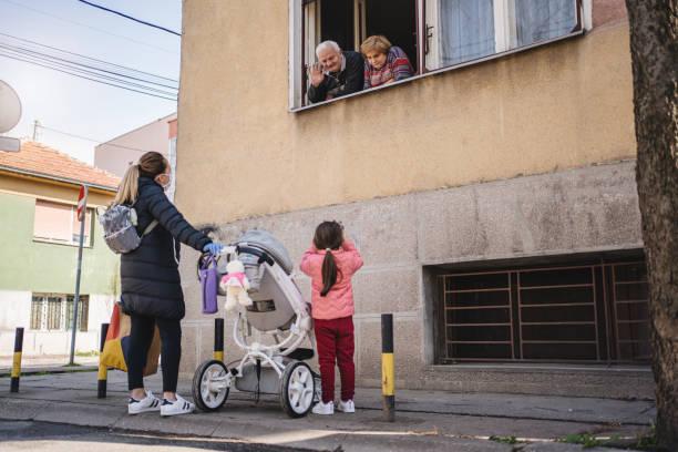 moeder en dochter die grootouders tijdens een coronavirusepidemie bezoeken - raam bezoek stockfoto's en -beelden