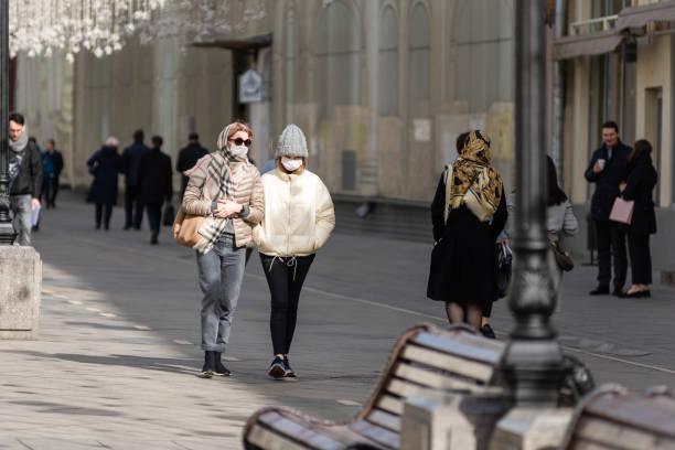 Mãe e filha caminham pela rua com máscaras médicas que protegem contra vírus - gripe, coronavírus e outros - foto de acervo