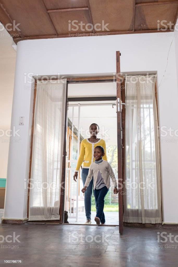 Mother and daughter walk in through front door of new home stock photo