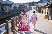 母と娘の成人の日に川に沿って歩く