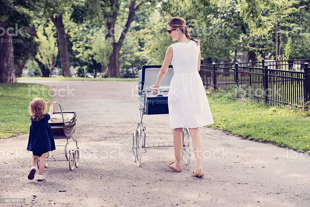 Mother and daughter walking babies in vintage prams. stock photo