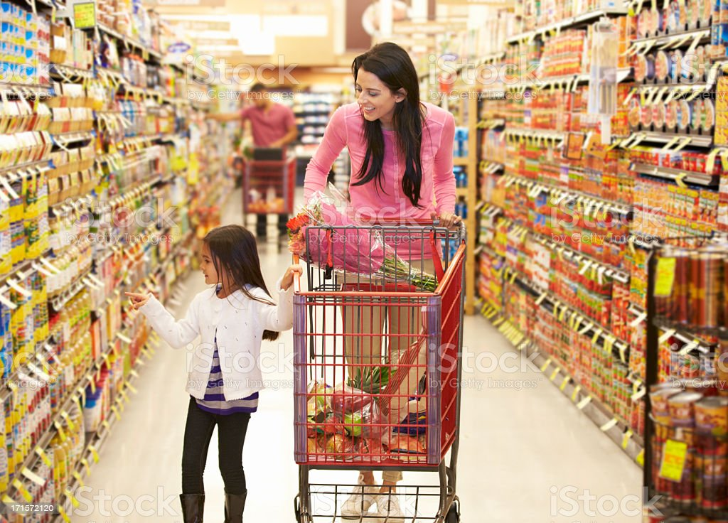 Madre e figlia a piedi lungo corridoio del supermercato di generi alimentari - foto stock