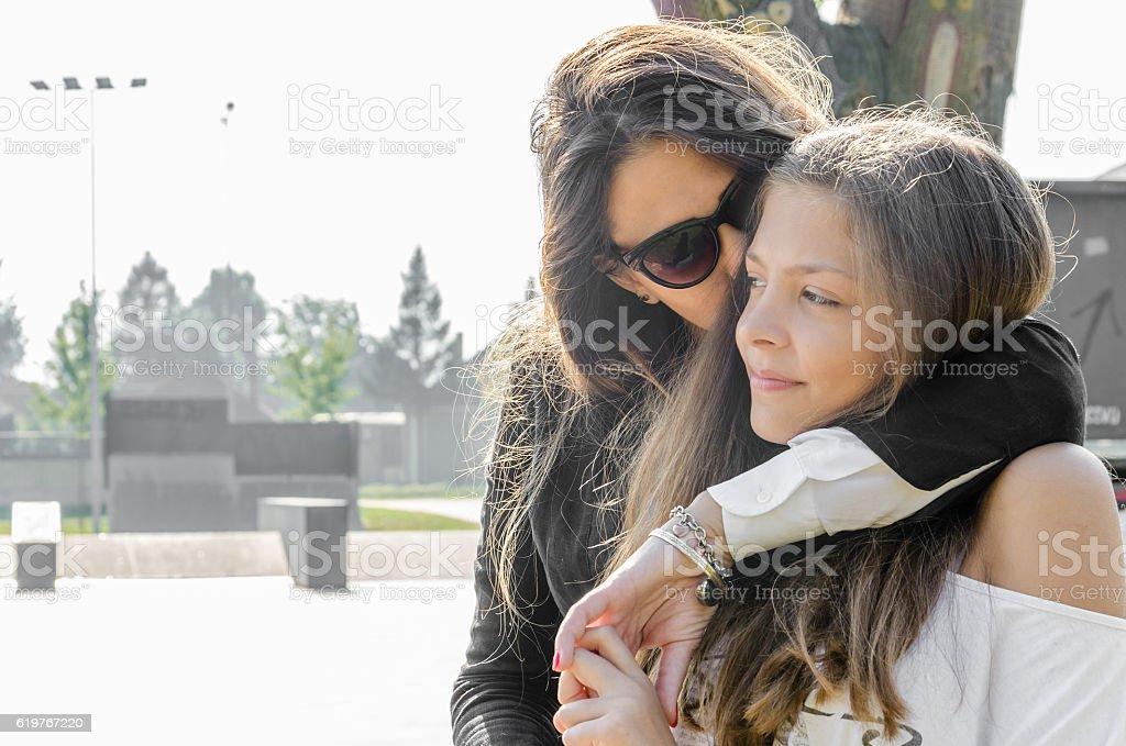 Mother and daughter walking embraced - foto de acervo
