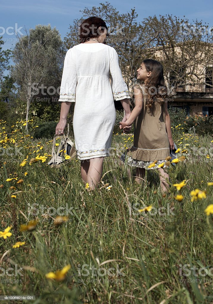 Mother and daughter (8-9) walking in meadow, rear view 免版稅 stock photo