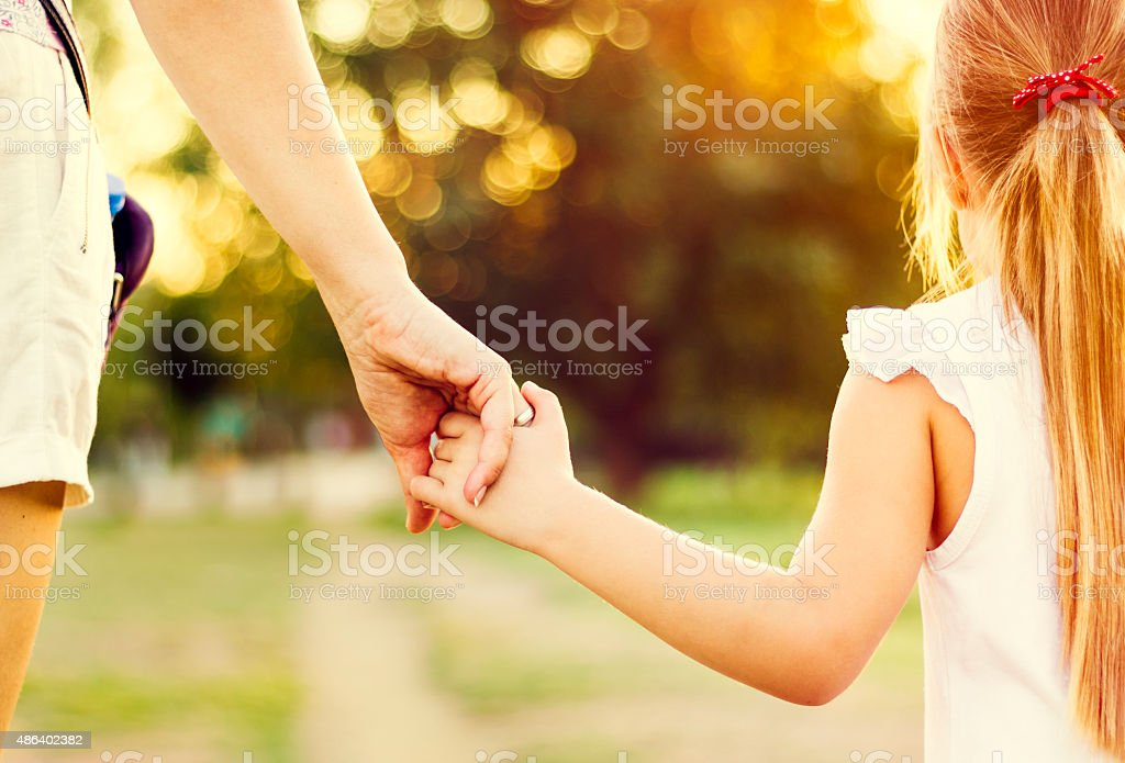 Mother and daughter walking in park closeup stock photo