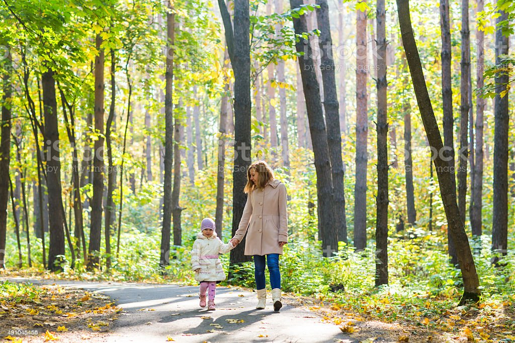 Mother and daughter walking in the autumn park stock photo