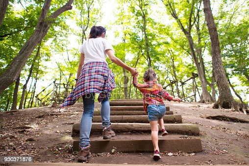 istock Mother and daughter walking in the forest 930371876