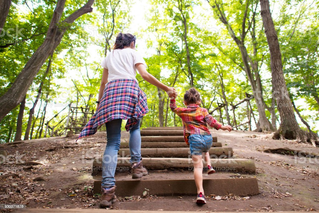 Mother and daughter walking in the forest stock photo