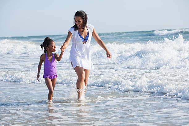 mãe e filha caminhando na surf - com os pés na água - fotografias e filmes do acervo