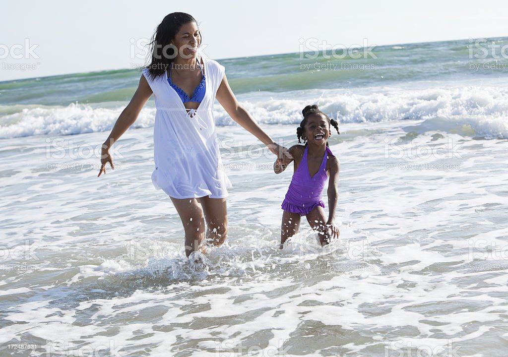 Mother and daughter walking in the surf royalty-free stock photo