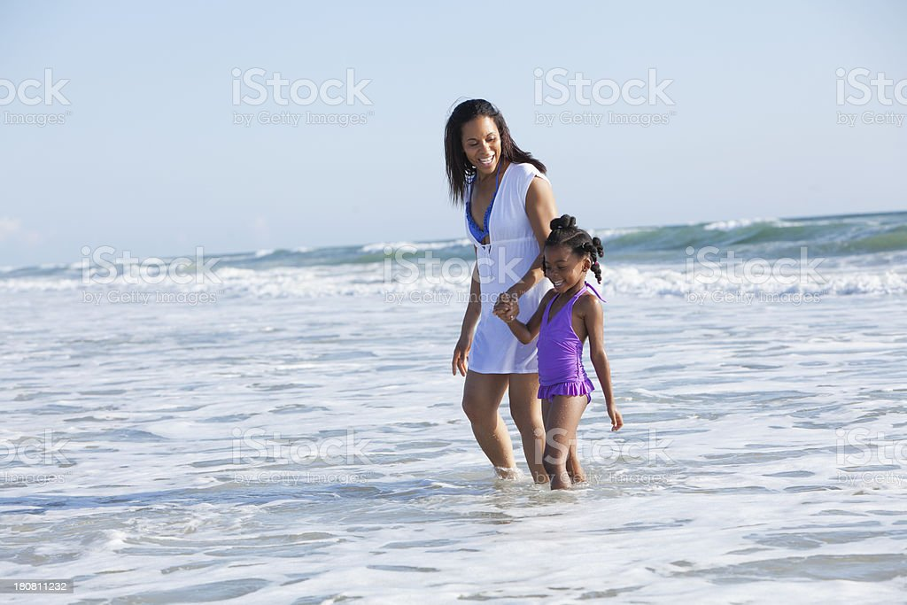 Mother and daughter walking in the surf stock photo