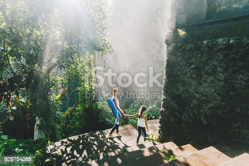 Asian mother and daughter walking in tropical park after yoga session in Bali, Indonesia
