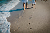 mother and daughter walking on beach leaving footprint in sand, family vacation