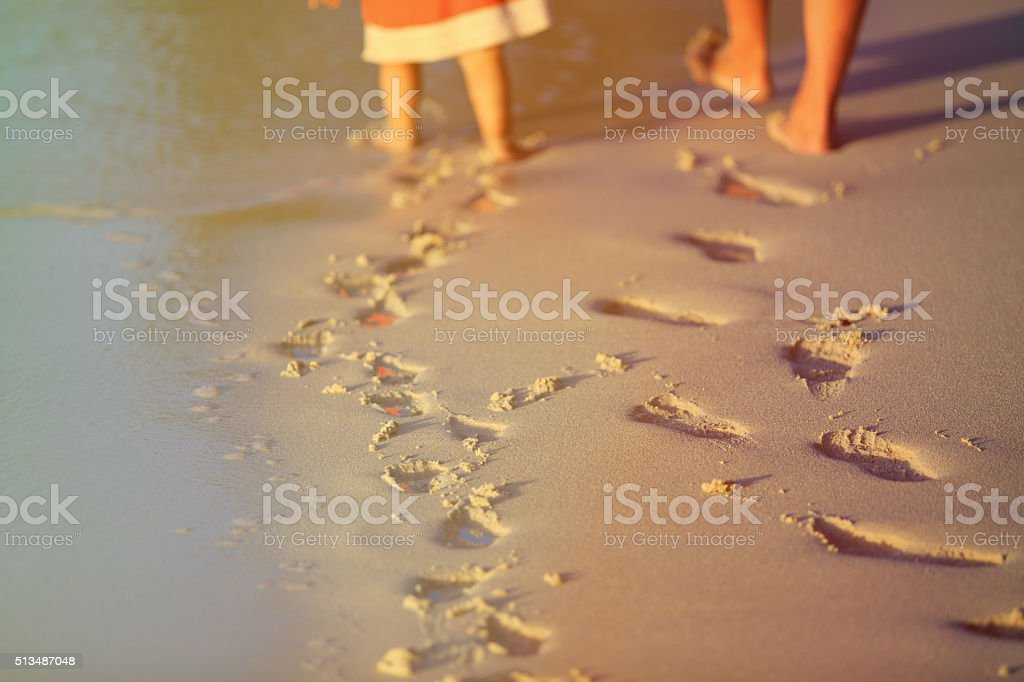 mother and daughter walking on beach leaving footprint in sand stock photo