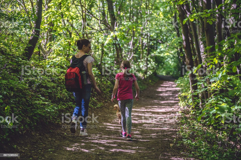 Mother and daughter walking on path in woods foto