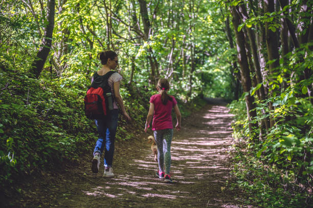 Mother and daughter walking on path in woods stock photo