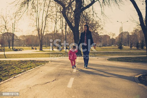 516318379 istock photo Mother and daughter walking through the park 938819128