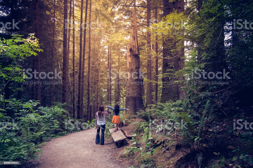 Mother and daughter walking together in Oregon forest stock photo
