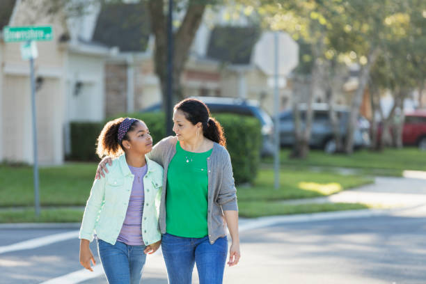 Mother and daughter walking together, talking A mature Hispanic woman, in her 40s, walking with her mixed race Hispanic and African-American 11 year old daughter outdoors in their residential neighborhood. Her arm is around her the girl's shoulders as they cross a street. They are looking at each other with serious expressions. Perhaps mom is giving her daughter a pep talk or offering some motherly advice. pre adolescent child stock pictures, royalty-free photos & images