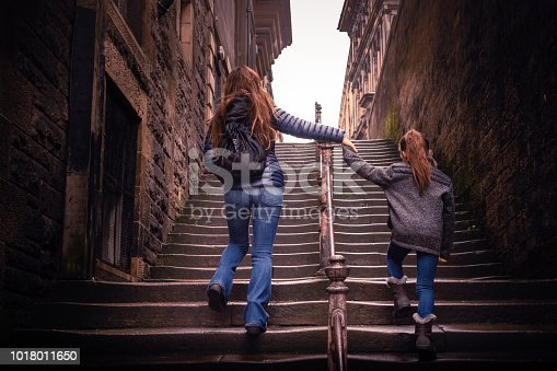 The mother is Chinese and her daughter is an 8 year old Eurasian girl. They are holding hands and walking up an old stone staircase between the gothic buildings of Edinburgh. They are tourists and exploring the city by foot. Although shot in June, it's cold and they're dressed in jackets and boots.