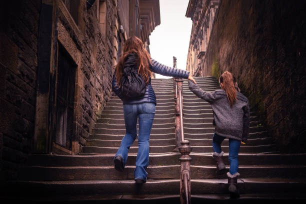 Mother and daughter walking up steps in Edinburgh, Scotland stock photo