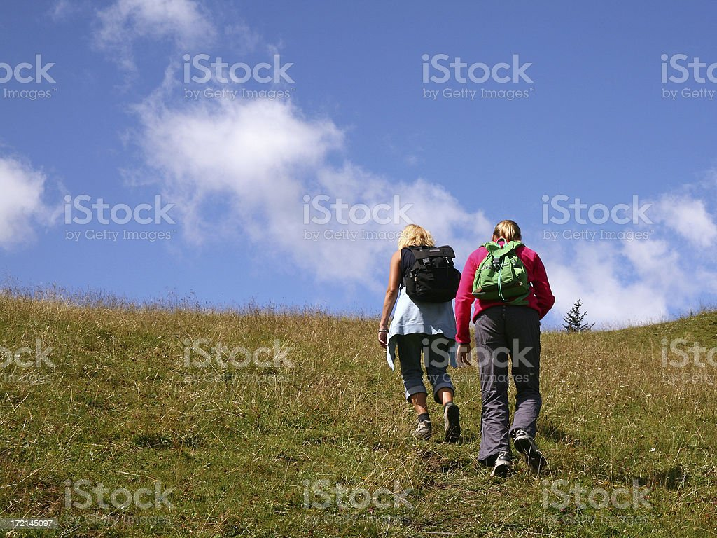Mother and daughter wandering on summer day approaching hill top royalty-free stock photo