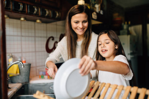 Mother and daughter washing dishes stock photo