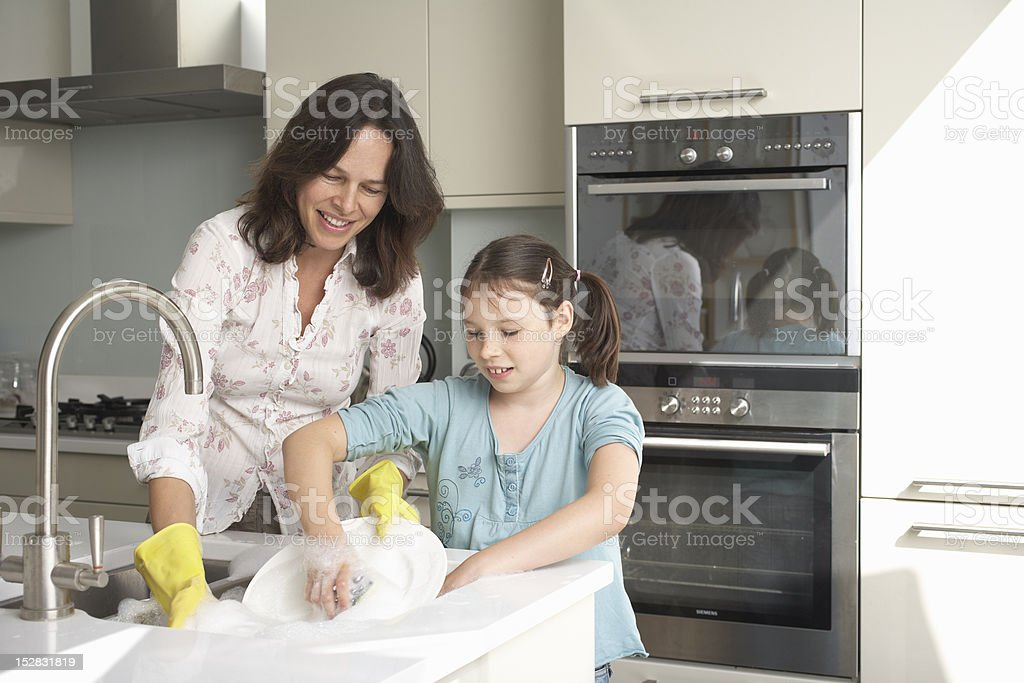 Mother and daughter washing dishes  10-11 Years Stock Photo
