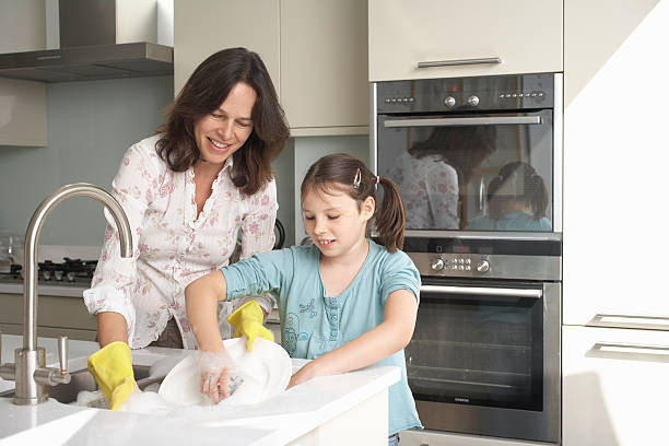 mother and daughter washing dishes - household chores stock photos and pictures