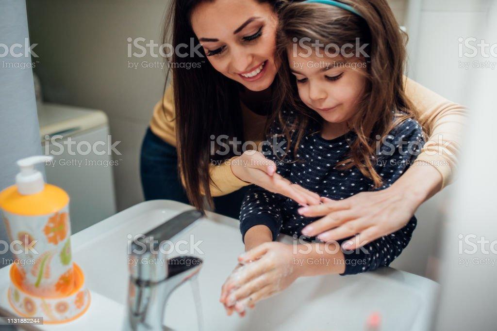 Mãos de lavagem da matriz e da filha - Foto de stock de Adulto royalty-free