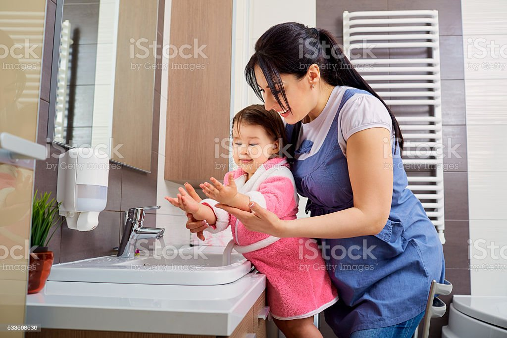 Mother and daughter washing their hands in the bathroom. stock photo