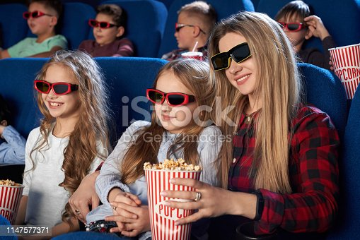 istock Mother and daughter watching 3D movie in cinema. 1147577371