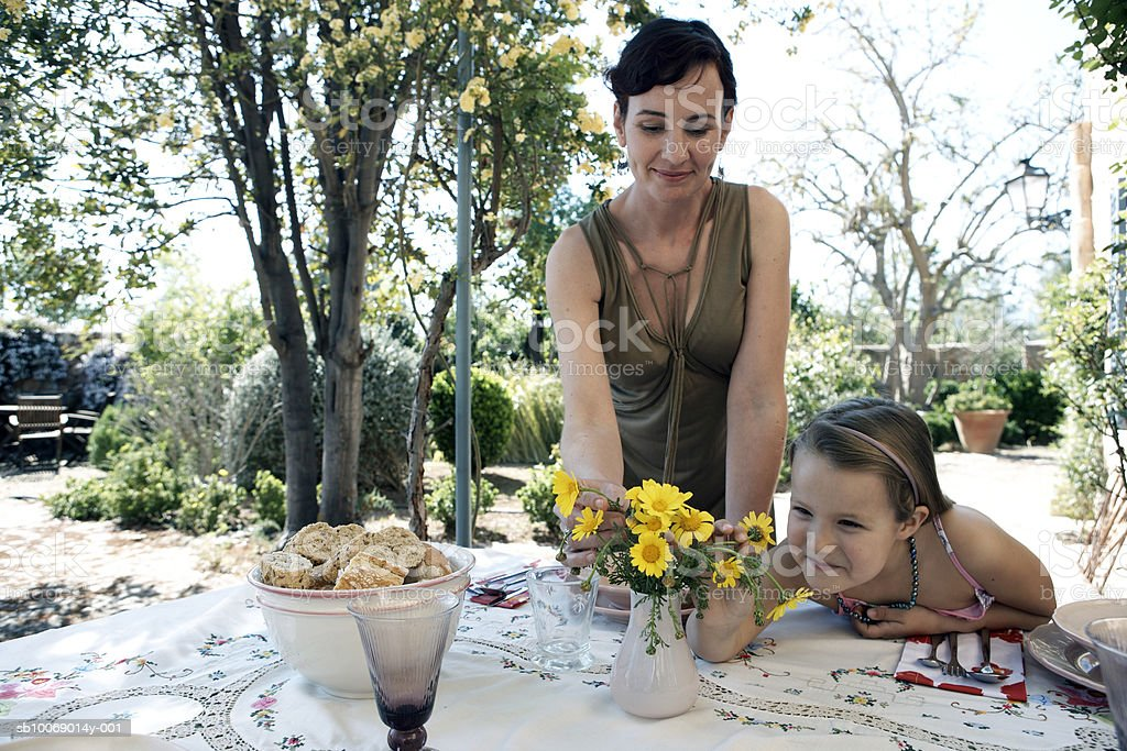 Mother and daughter (8-9) watching flowers in vase outdoors 免版稅 stock photo