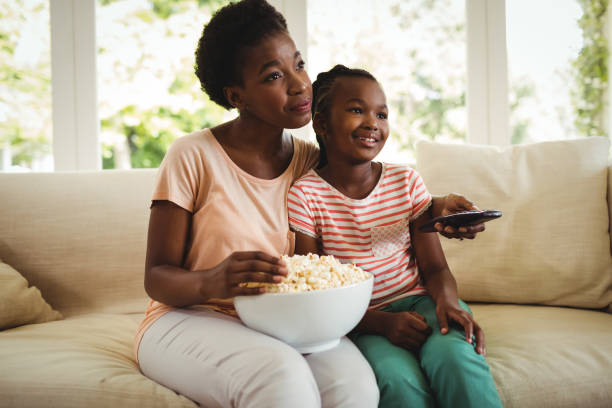Mother and daughter watching television in living room stock photo