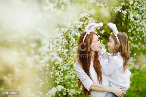 istock Mother and daughter wearing bunny ears on Easter 513303626