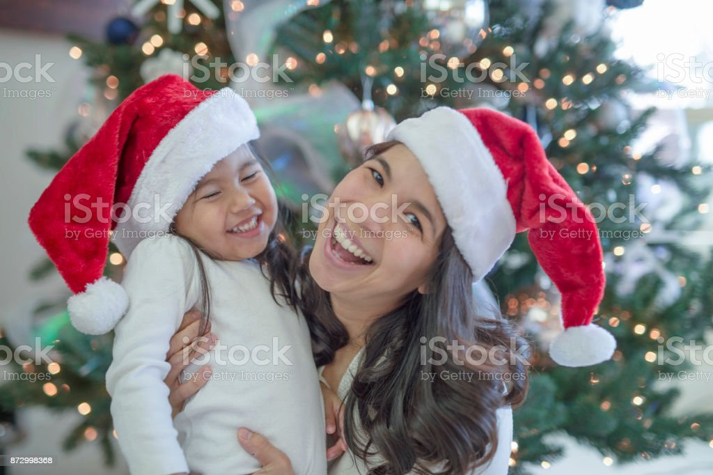 21fe17cde Mother And Daughter Wearing Santa Hats And Laughing Stock Photo ...