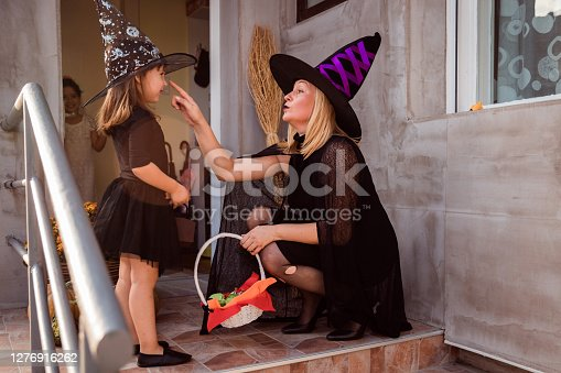 Happy child looking at her mother, both wearing Halloween costumes in front of the house