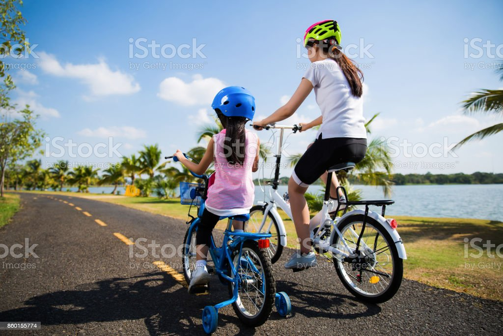 Mother and daughter were cycling at the park in the morning. stock photo