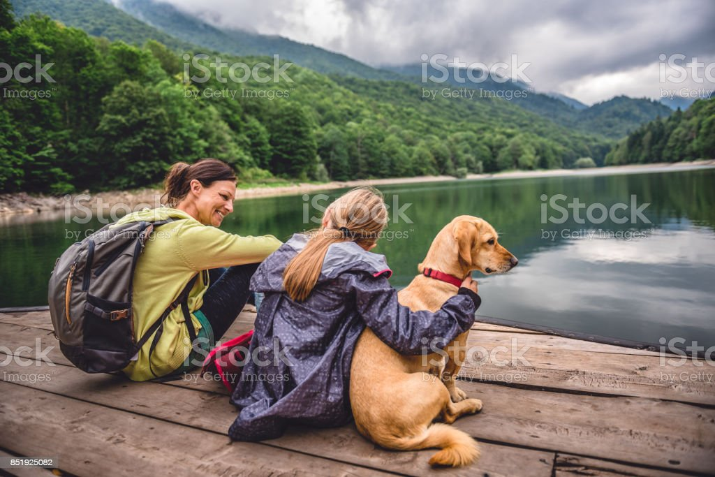 Mother and daughter with a dog resting on a pier stock photo