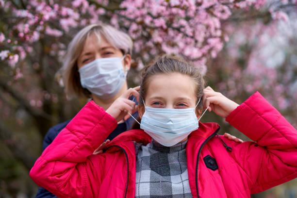 madre e hija con una máscara facial están en la ciudad al aire libre, árboles en flor, temporada de primavera, tiempo de floración - concepto de alergias y protección de la salud contra el aire polvoriento - foto de stock