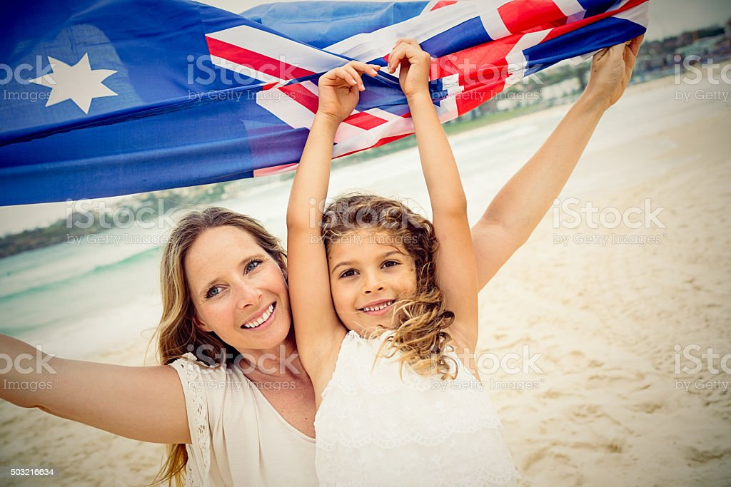 Mother and daughter with Australian flag at the beach, Australia stock photo
