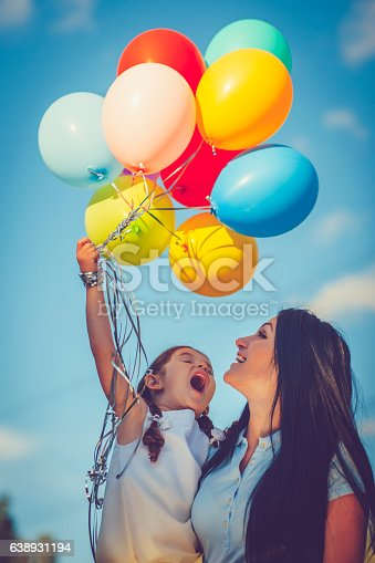 Young woman and girl with colorful balloons in park in summer