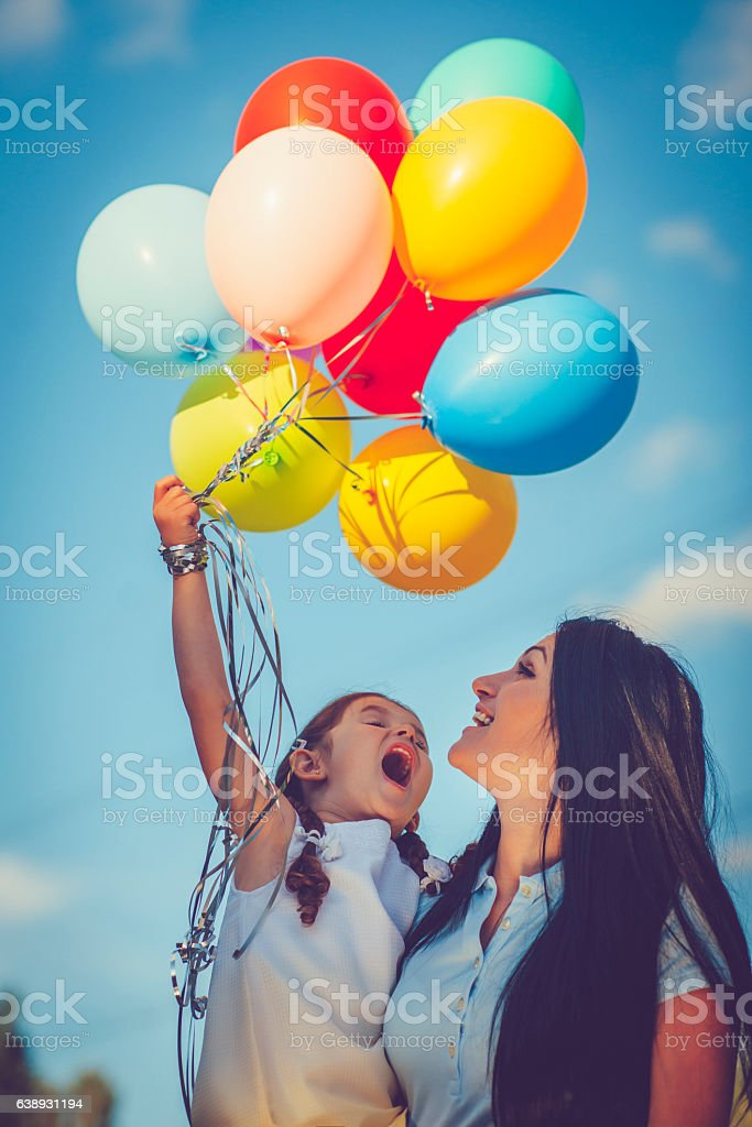 Mother and daughter with balloons stock photo