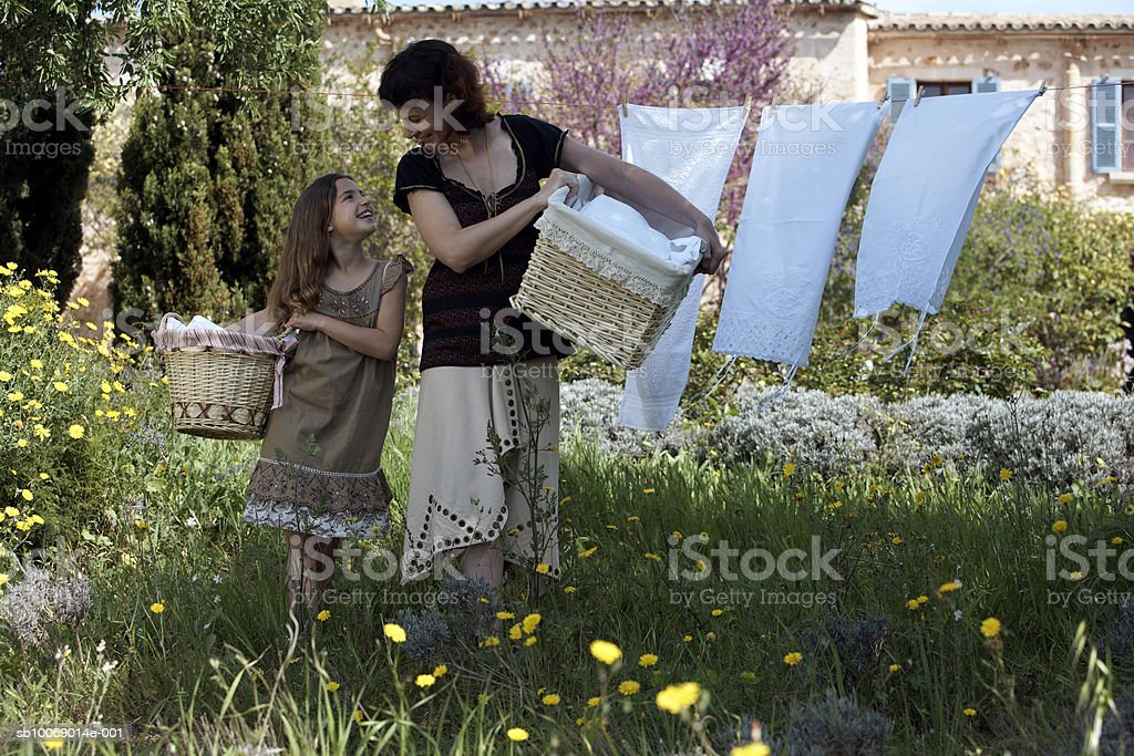 Mother and daughter (8-9) with baskets in domestic garden royalty-free stock photo