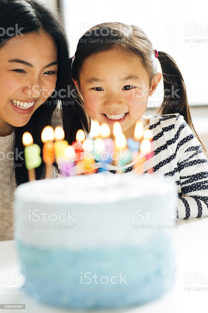 Mother and daughter with birthday cake stock photo