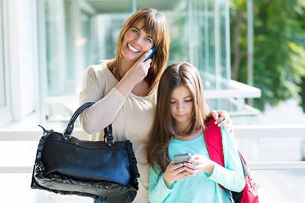 mutter und tochter mit cel telefone - kinderhandtaschen stock-fotos und bilder