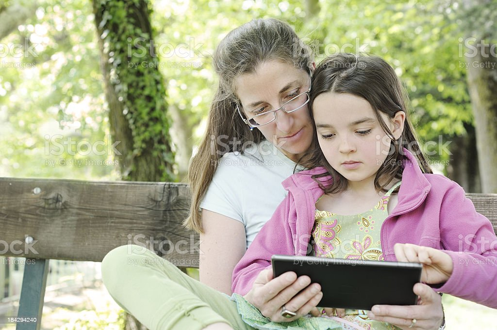 Mother and daughter with digital tablet outdoors royalty-free stock photo