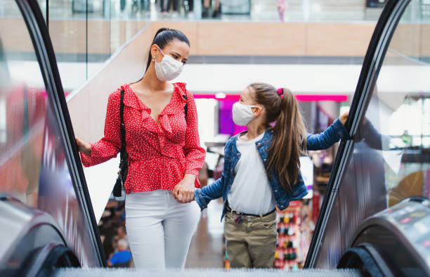Mother and daughter with face mask on escalator indoors in shopping center, coronavirus concept. stock photo