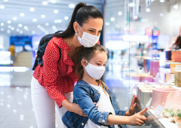 Mother and daughter with face mask standing indoors in shopping center, coronavirus concept. stock photo